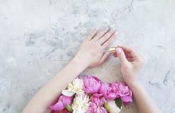 Peonia cosmetica del fiore delle mani del manicure della crema di igiene dell'idratante femminile di estate su fondo concreto gri immagine stock libera da diritti