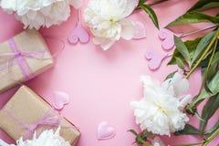 Peonie bianche con i contenitori di regalo e cuori decorativi su un rosa Fotografia Stock Libera da Diritti
