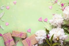 Peonie bianche con i contenitori di regalo e cuori decorativi sul BAC verde Fotografia Stock Libera da Diritti