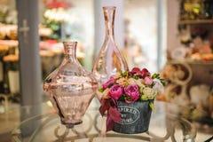 Peonie e vaso rosa sulla tavola Fotografia Stock
