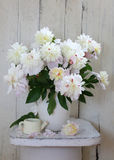 Peonies. Bunch of peonies on wooden background. Peonies. Bouquet of peonies in white jug on wooden background Stock Photography