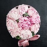 Peonies flowers in a gift box. Fresh pink peonies flowers in a white gift box with ribbon on dark surface, flat lay Royalty Free Stock Photography