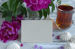 Peonies flowers pink glass of tea with greeting card marshmallow on a white wooden background - stock image. Stock Photography