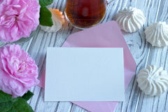 Peonies flowers pink glass of tea with greeting card marshmallow on a white wooden background - stock image. Stock Photos