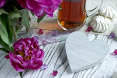 Peonies flowers pink glass of tea with white wooden heart marshmallow on a white wooden background - stock image. Royalty Free Stock Photos