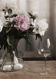 Peonies in the glass vase, wine glass Royalty Free Stock Image