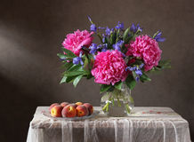Peonies, irises and peaches. Still life with peonies, irises and peaches. Garden flowers in a jug and fruit Stock Photos