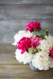 Peonies in a wicker vase on the boards Stock Photo
