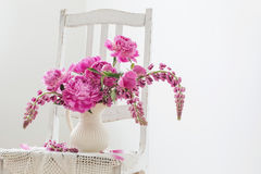 Peony flowers in   vase on vintage chair Stock Photography