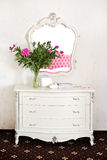 Peony flowers on a white commode under a mirror Stock Photos
