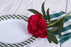 Peony and white plate on a wooden table Royalty Free Stock Photos