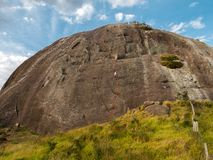 People abseiling a steep rock mountain wall in Brazil. People abseiling a steep rock mountain wall stock photography