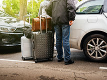 People adding multiple luggage in car trunk parked city. Low section of group of seniors and adults loading luggage in estate car parked city Stock Images