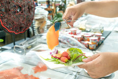 People adding topping for smoked salmon salad at food line in ho Royalty Free Stock Images