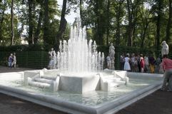 People admiring marble fountain and statues in the Summer Garden royalty free stock images