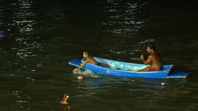 People adult and kid are boating looking for krathong in the river find coin or money and them keep all krathong is not nature obj. Ect go to trash 4k25fps
