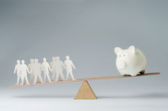 People against money. Men balanced on seesaw over a piggy bank Stock Photos