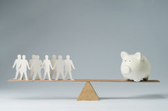People against money. Men balanced on seesaw over a piggy bank Royalty Free Stock Image