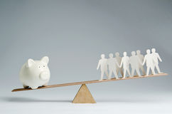 People against money. Men balanced on seesaw over a piggy bank Stock Image