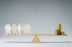 People against money. Men balanced on seesaw over a stack of coins Royalty Free Stock Images