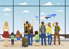People against windows of an airport observation deck looking at plane taking off Stock Image