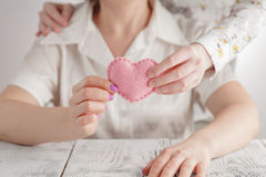 People, age, family, love and health care concept - close up of senior woman and young woman hands holding red heart Royalty Free Stock Photos