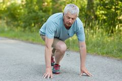 People, age and sport motivation concept. Strong fit grey haired man ready to start jogging or race, participates in competitions, Royalty Free Stock Image