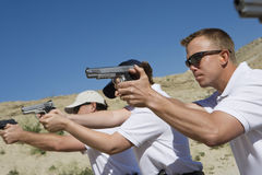 People Aiming Hand Guns At Firing Range. During weapons training Stock Image
