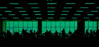 People in the airport. Silhouette of Crowded People at the Airport. Many tourists waiting at the terminal for boarding time. Panorama with green filter stock photography