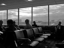 People at airport waiting for fllight, vertical. Businessmen waiting at airport for flight: business travel, getting home for the holidays Royalty Free Stock Photos