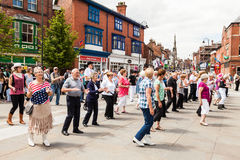 People of all ages line dancing in the street. Stock Images