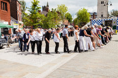 People of all ages line dancing in the street. Royalty Free Stock Photography
