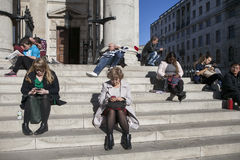 People of all ages are sitting on the steps near Trafalgar Square, relaxing and sunbathing in the sun Stock Photos