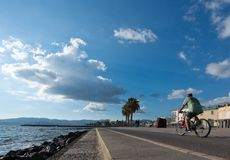 People along the Portixol promenade. PORTIXOL, MALLORCA, BALEARIC ISLANDS, SPAIN - SEPTEMBER 27, 2017: People out and about along the promenade on a sunny day on Royalty Free Stock Photos