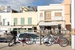 People along the Portixol promenade. PORTIXOL, MALLORCA, BALEARIC ISLANDS, SPAIN - SEPTEMBER 27, 2017: People out and about along the promenade on a sunny day on Royalty Free Stock Image