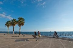 People along the Portixol promenade. PORTIXOL, MALLORCA, BALEARIC ISLANDS, SPAIN - SEPTEMBER 27, 2017: People out and about along the promenade on a sunny day on Stock Photos