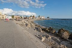People along the Portixol promenade. PORTIXOL, MALLORCA, BALEARIC ISLANDS, SPAIN - SEPTEMBER 27, 2017: People out and about along the promenade on a sunny day on Stock Images