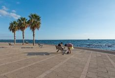 People along the Portixol promenade. PORTIXOL, MALLORCA, BALEARIC ISLANDS, SPAIN - SEPTEMBER 27, 2017: People out and about along the promenade on a sunny day on Stock Photography