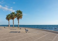 People along the Portixol promenade. PORTIXOL, MALLORCA, BALEARIC ISLANDS, SPAIN - SEPTEMBER 27, 2017: People out and about along the promenade on a sunny day on Stock Photo