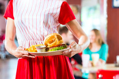 People in American diner or restaurant eating fast food Royalty Free Stock Image