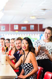 People in American diner or restaurant with milk s. Friends or couples eating fast food and drinking milk shakes on bar in American fast food diner, the waitress royalty free stock photos