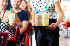 People in American diner or restaurant with milk shakes. Friends or couples eating fast food and drinking milk shakes on bar in American fast food diner, the stock image