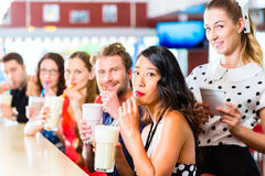 People in American diner or restaurant with milk shakes Royalty Free Stock Photo