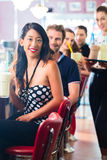 People in American diner or restaurant with milk shakes Royalty Free Stock Photography