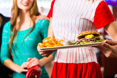 People in American diner or restaurant and waitress Stock Images
