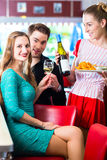 People in American diner or restaurant with wine. Friends or couple eating fast food in American fast food diner, the waitress serving the food and wine Royalty Free Stock Photography