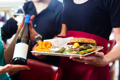 People in American diner or restaurant with wine Royalty Free Stock Images