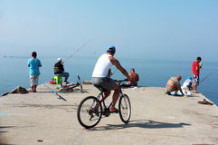 People angling on pier. Group of fishing enthusiasts angle early morning on pier while a man on his bicycle watching them in Akcay,  Turkey Royalty Free Stock Photography