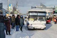 People in anticipation of public autobus are standing on carriageway of city road in bus stop area Stock Photography