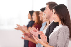 People applauding. Side view of group of cheerful young people standing in a row and applauding to someone royalty free stock photography